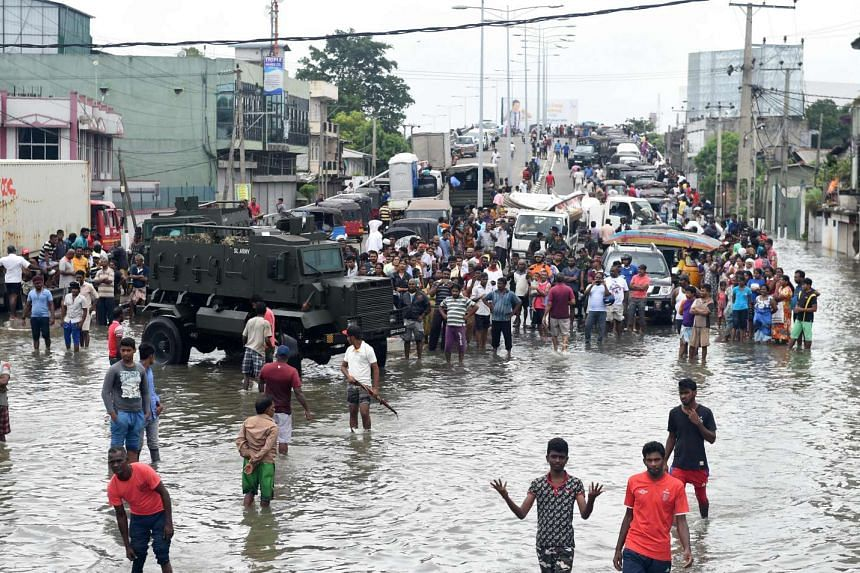 Sri Lankan residents make their way through floodwaters in Colombo on May 19, 2016.