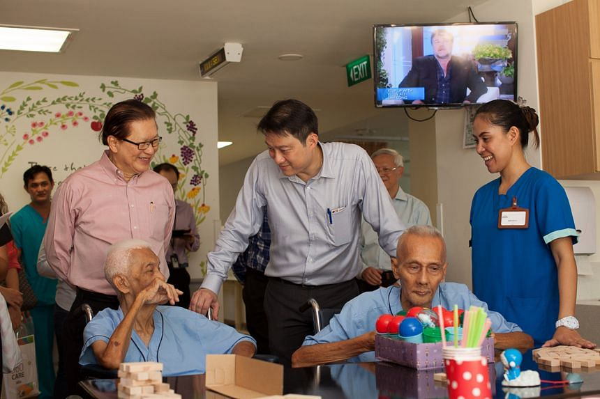Minister of State for Health Dr Lam Pin Min chats with two residents of All Saints Home while on a tour of the new centre in Jurong East with Chairman of All Saints Home Mr Chua Hung Seng on May 20.