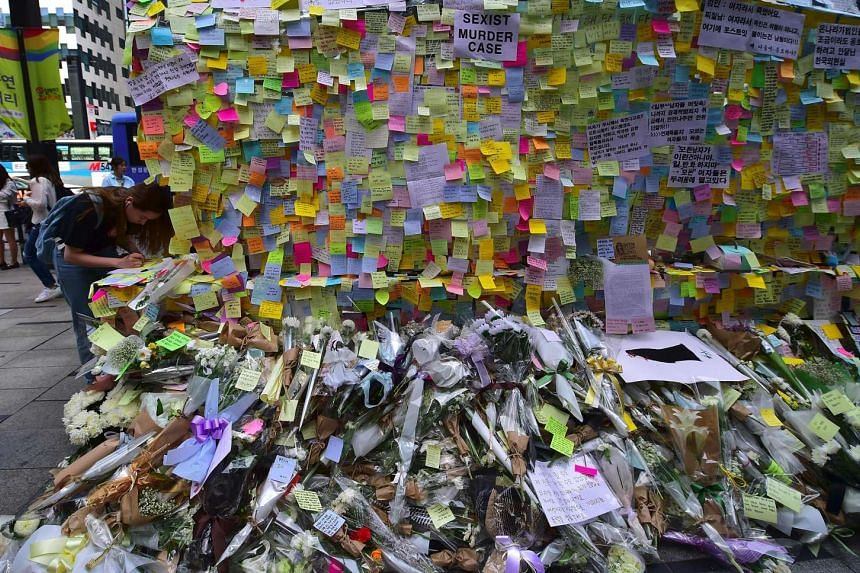 South Koreans leaving messages written on post-it notes at an exit of Gangnam subway station, which has been turned into a mini shrine for a 23-year-old woman who was stabbed to death by a stranger in a nearby public bathroom, in Seoul, on May 20, 20