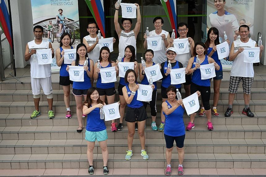 Ms See (front row, centre) and other F&N Foods staff holding up 100Plus cold towels. The towels, handed out while stocks last to the first 8,000 finishers, will be available at a 100Plus cool zone at the ST Run in the City on Sunday.