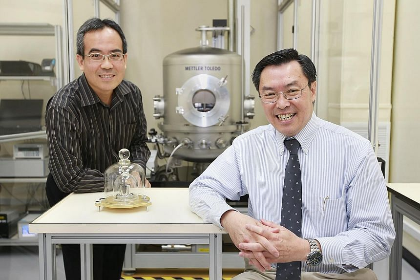The National Metrology Centre's Mr Lee (far left) and Dr Liew with a 1kg prototype.