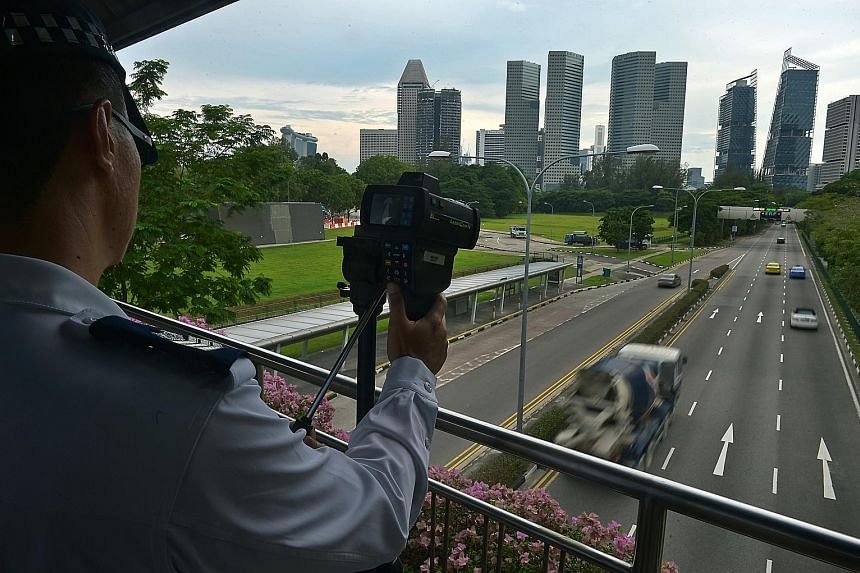 A Traffic Police officer operating the new speed laser camera on a bridge over Nicoll Highway yesterday.