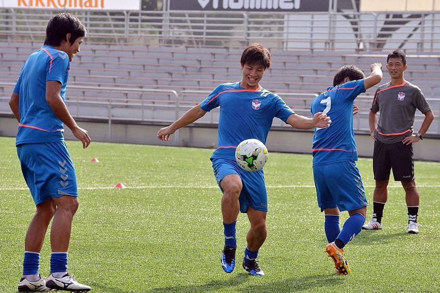 Albirex Niigata forward Atsushi Kawata (centre) controlling the ball in training at Jurong East Stadium as his coach Naoki Naruo (right) looks on. The league's leading striker aims to win the Golden Boot and also fire his side to their first S-League