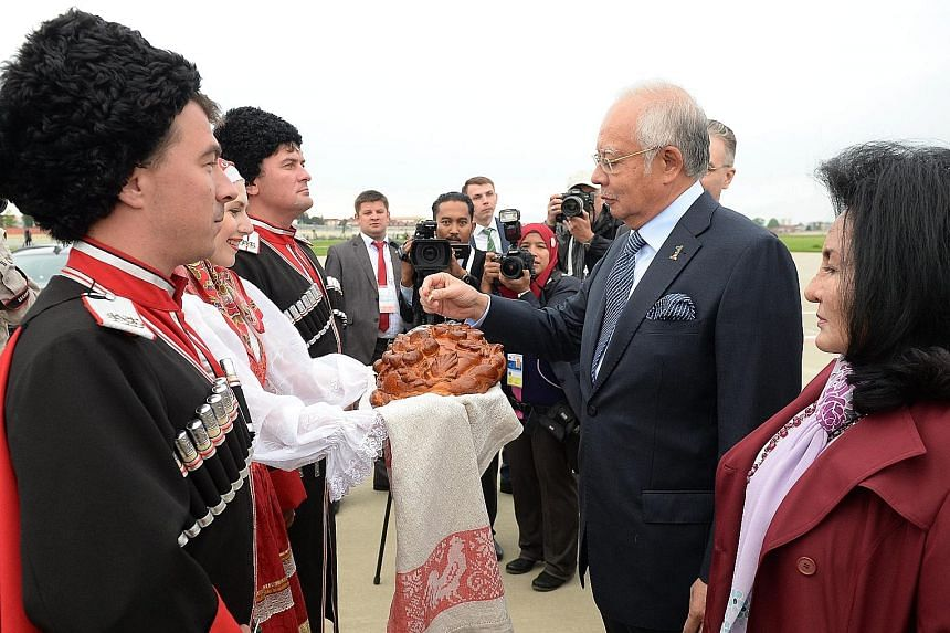 Malaysian PM Najib and his wife Rosmah Mansor taking part in the traditional bread and salt welcome ceremony on their arrival at Sochi on Wednesday.