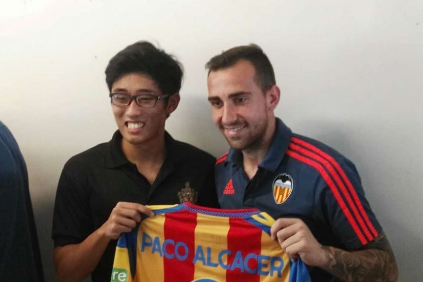 Spanish striker Paco Alcacer poses with Jonathan Chua after giving him his jersey.