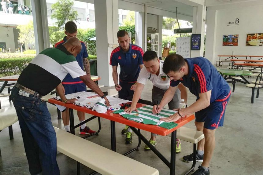 Valencia players signing on jerseys to surprise Jonathan Chua, whose act of honesty at the Schools National A Division football championships drew praise.