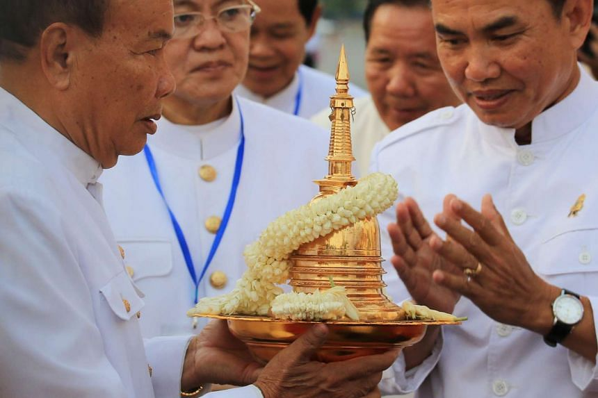 Cambodian Minister of Cults and Religion Him Chhem (left) holds an urn believed to contain the ashes of Buddha in the Visak Bochea Day celebrations in Phnom Penh, on May 20, 2016.