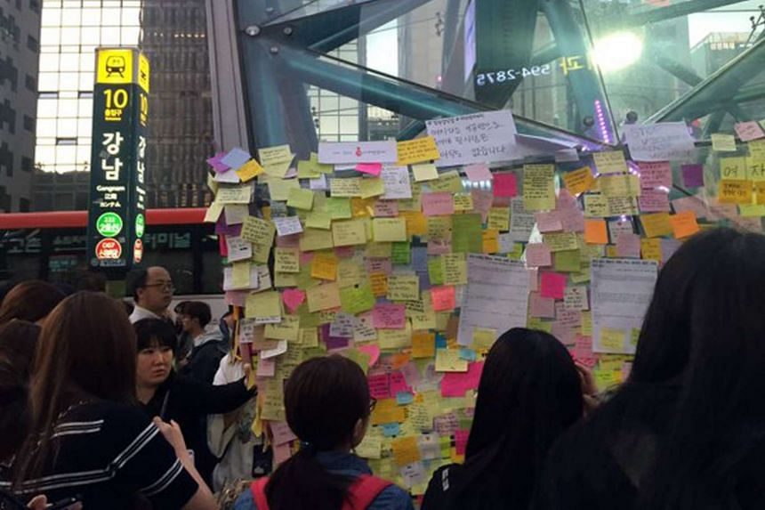 Passers-by looking at post-it notes that covered a wall at Gangnam Station in Seoul, in memory of a woman who was murdered in a nearby building on May 17, 2016.