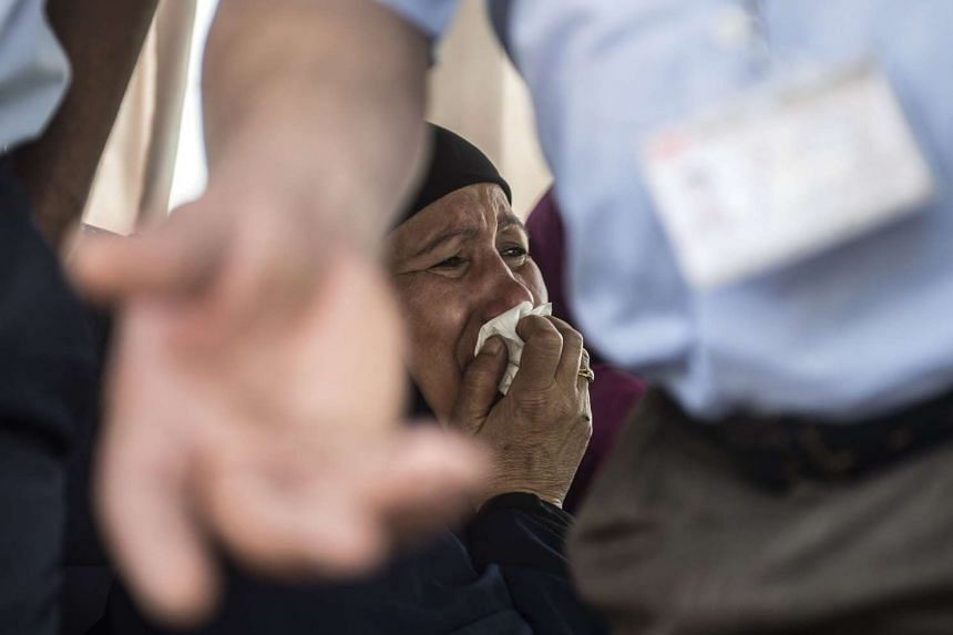 A relative of a passenger cries as family members are transported by bus to a gathering point at Cairo airport on May 19, 2016.