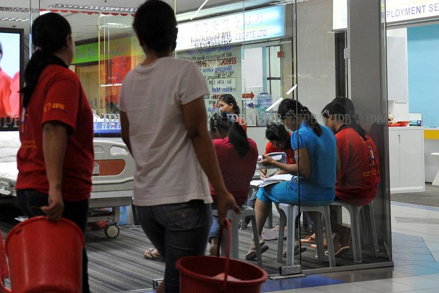 Maids who are undergoing training, seen seated inside a maid agency at Bukit Timah Shopping Centre on Sept 10, 2014.