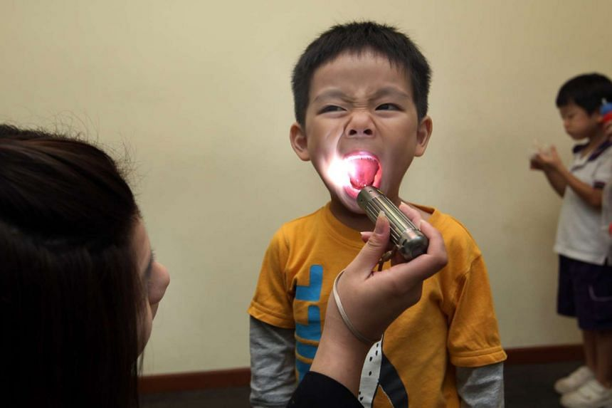 A boy being checked for symptoms of hand, foot and mouth disease before entering the classroom.