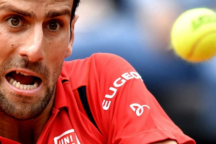 Serbia's Novak Djokovic eyes the ball during his match against France's Stephane Robert during the ATP Tennis Open tournament at the Foro Italico, on May 11, 2016 in Rome.