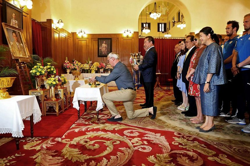 Leicester City's manager Claudio Ranieri (centre) kneels as he pays his respects to a picture of Thai King Bhumibol Adulyadej during a visit to the Grand Palace in Bangkok on May 19, 2016.