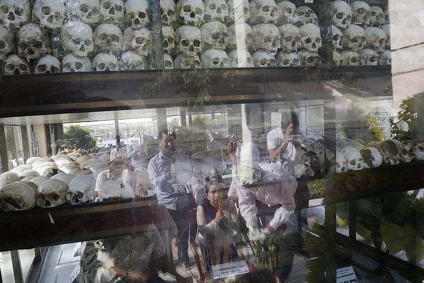 A group of Cambodians offering prayers is reflected in the glass cover of a stupa at the Choeung Ek Genocidal Centre, on the outskirts of Phnom Penh. Cambodia marked its annual Anger Day yesterday to commemorate the victims of the Khmer Rouge regime