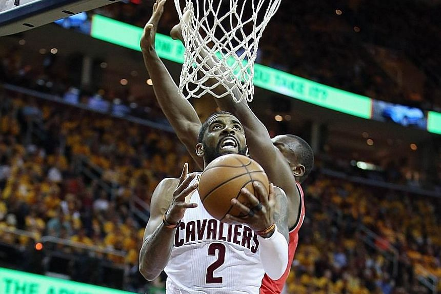 Kyrie Irving shoots from under the basket for two of his game-high 26 points to help the Cleveland Cavaliers to a 10th straight win this NBA post-season.