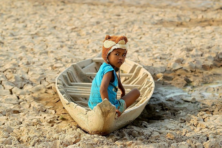 A girl sitting in a boat on a dried-up pond in the drought-hit Kandal province in Cambodia. Cambodia is grappling with soaring temperatures and its worst drought in decades. Eighteen of the country's 25 provinces are suffering from water shortage as