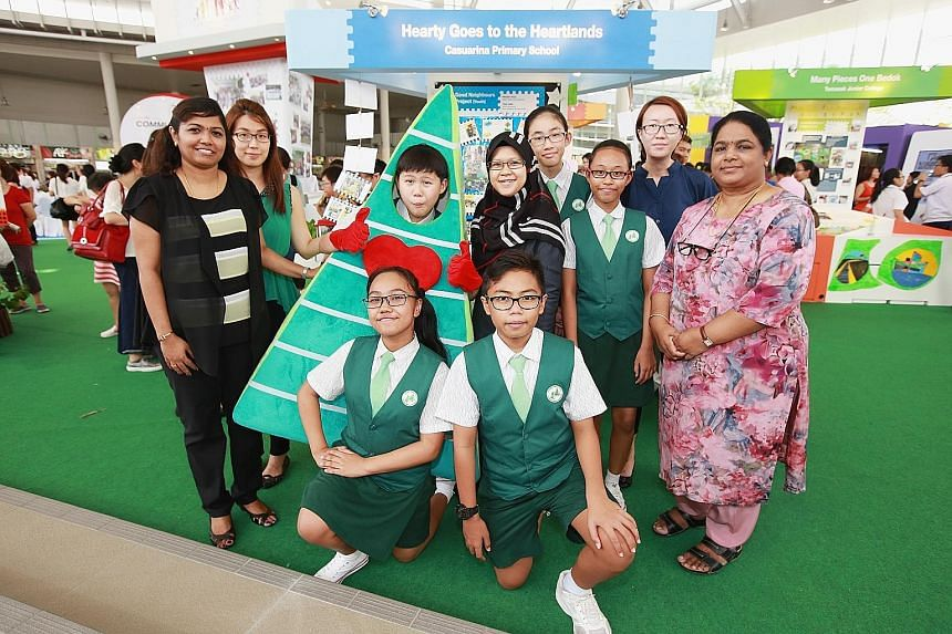 At Bedok Town Plaza's opening are Casuarina Primary School's (kneeling, from left) Diyanah Amani Ismail and Muhd Zharfan Shahrin; (standing, from left) Madam Kaladevi Nadarajah, Ms Ng Wei Hunn, Lee Pin, Madam Maryana Mohamad, Ng Yen Nee, Sufia Namira