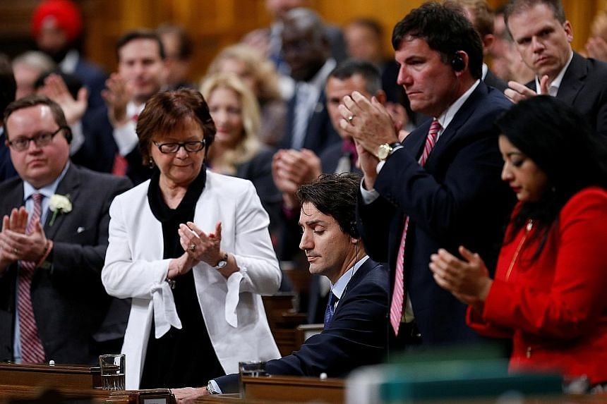 Members of the Liberal caucus applauding Mr Trudeau (seated) after he delivered his apology on Thursday. The Canadian Prime Minister said he was only human and promised that there would be no repeat of his actions.