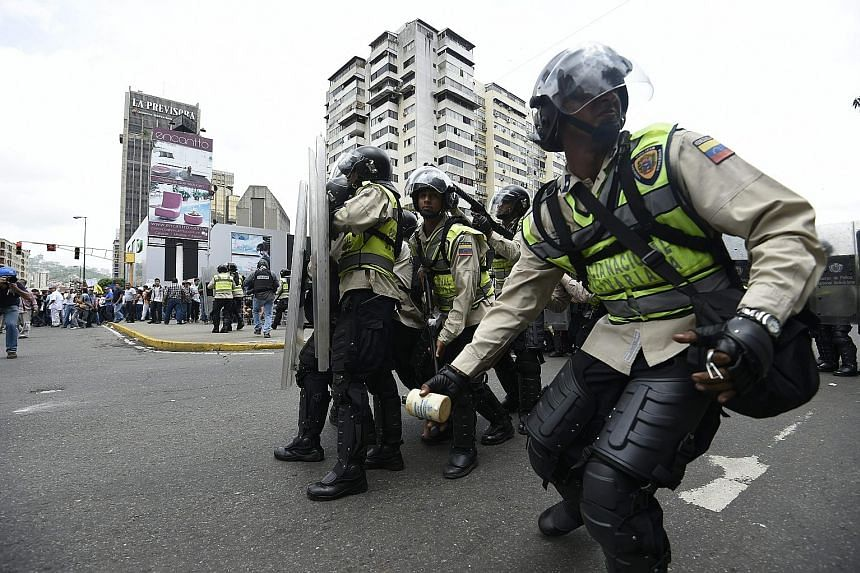 Venezuelan police in a face-off with protesters in Caracas on Wednesday. Rising political and economic tensions are gripping a country beset by record inflation, shortages of basic goods, and currency controls.