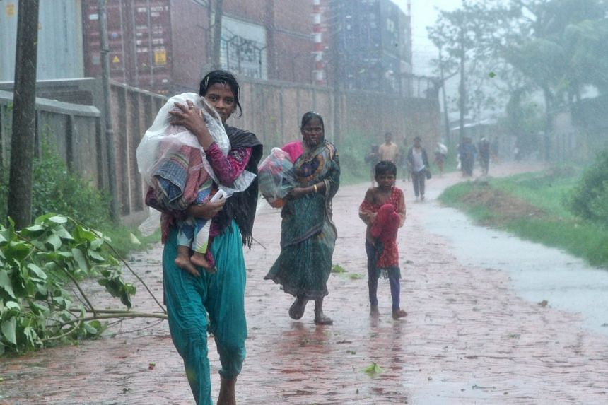 People walk in the streets in the rain as they look for shelter as Cyclone Roanu hits Chittagong, Bangladesh, on May 21, 2016.