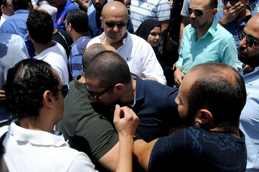 Family and friends of the victims gather for an absentee funeral prayer at a mosque near Cairo airport.