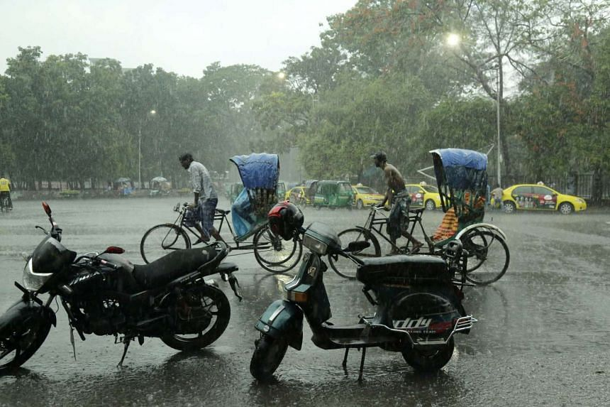 Rickshaw pullers carry passengers during a downpour in Dhaka, Bangladesh, on May 13, 2016.