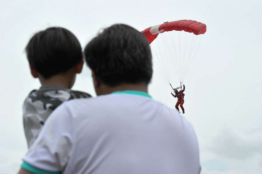 Visitors watching a member of the SAF Red Lions Parachute Team at the RSAF Open House at Paya Lebar Air Base, on May 21, 2016.