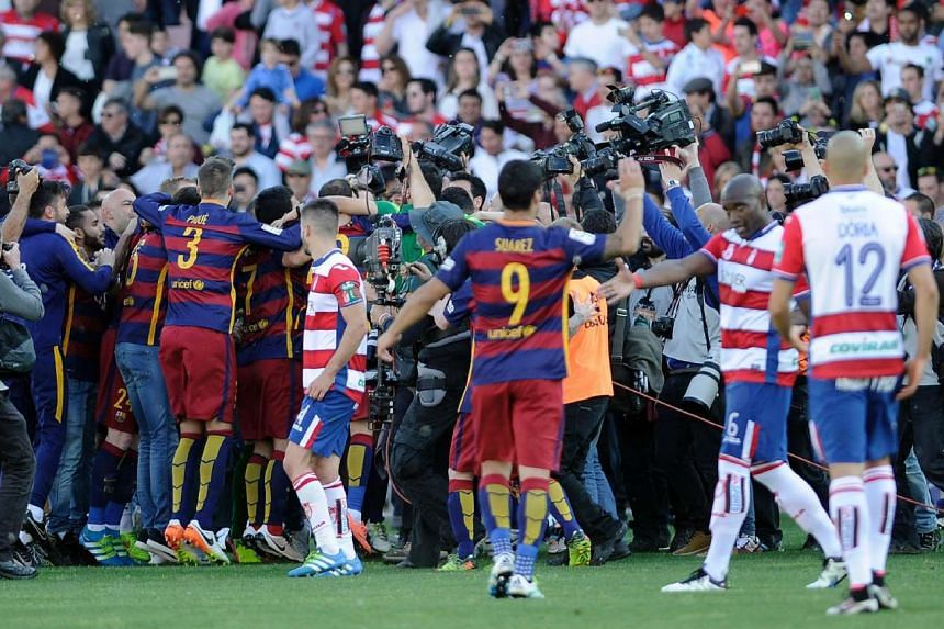 Barcelona's players celebrate their 24th La Liga title at the end of the Spanish league football match in Granada, on May 14, 2016.
