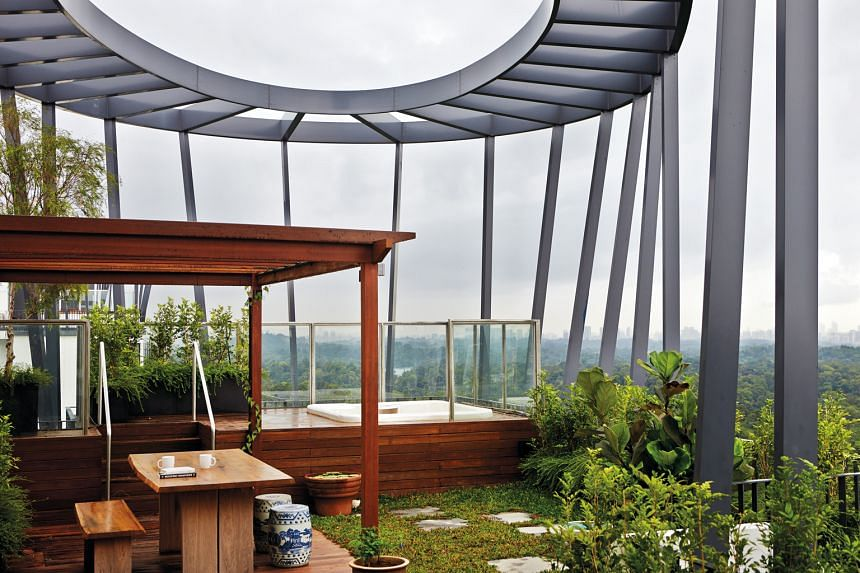 Lush greenery and a wooden deck on the rooftop terrace combine to give the space a resort vibe.