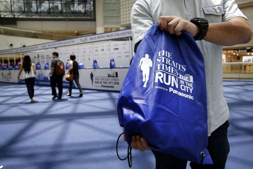 A staff displaying the ST Run Race Pack at the collection booth at Raffles City atrium on May 12, 2016.