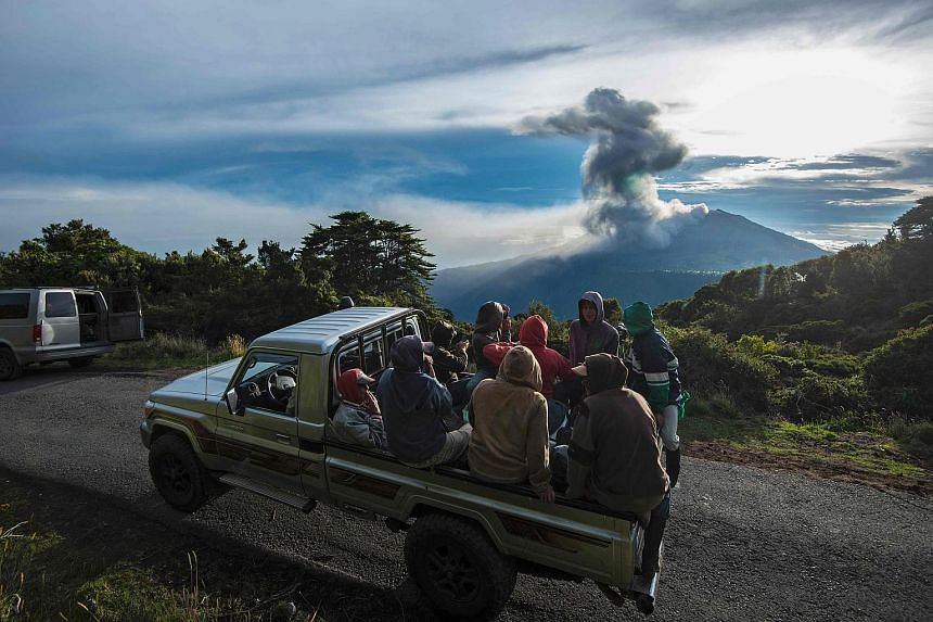 Farmers are transported on the back of a truck as the Turrialba volcano erupts in the background on May 20, 2016, in Cartago, Costa Rica.