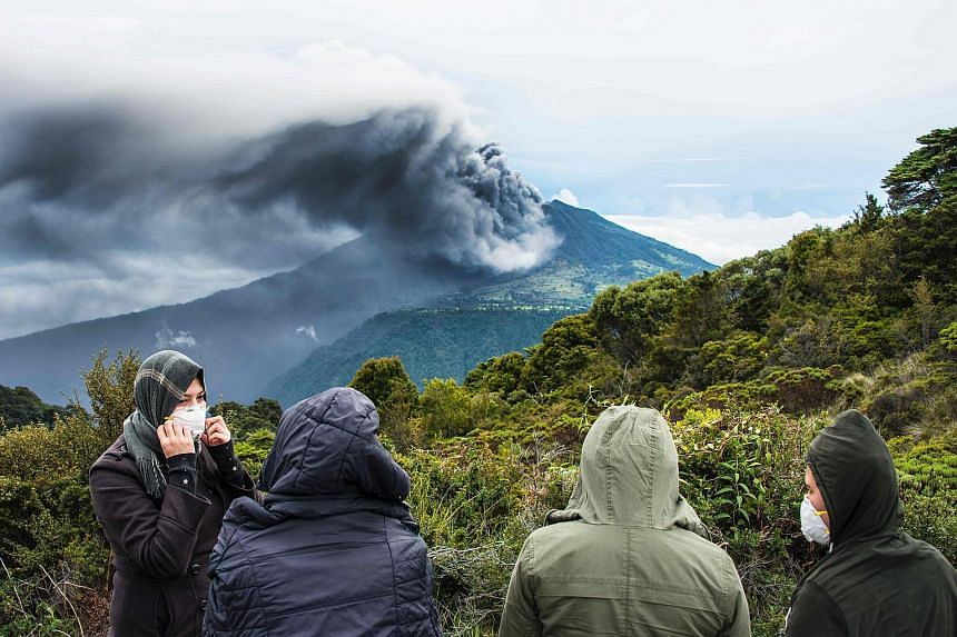 People looking at the Turrialba volcano as it spewes ashes on May 20, 2016, in Cartago, Costa Rica.