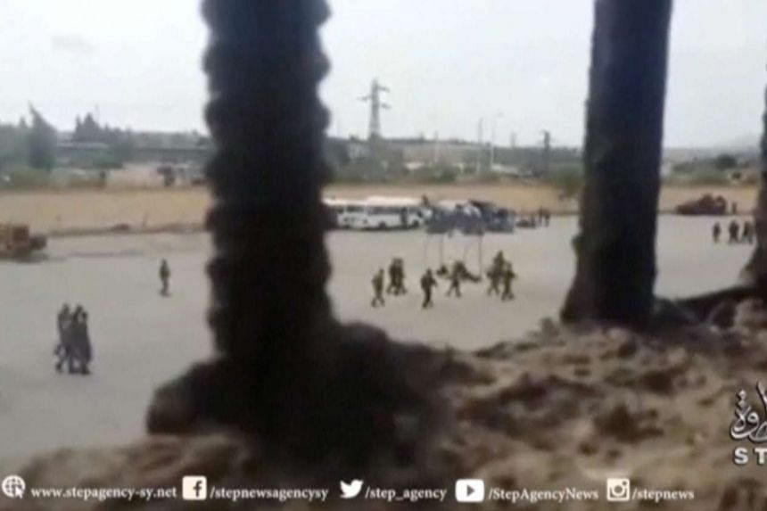 A still image taken from a video uploaded on a social media website shows what it says are government security forces walking outside Hama prison in Syria on May 7, 2016 after a revolt by its inmates.