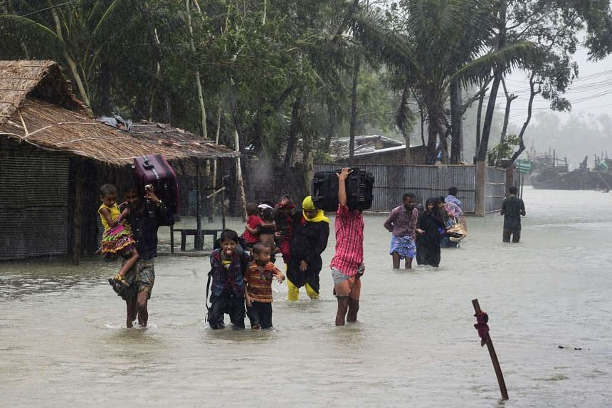 Bangladeshi villagers make their way to shelter in Cox's Bazar on May 21, 2016, as Cyclone Roanu approached.