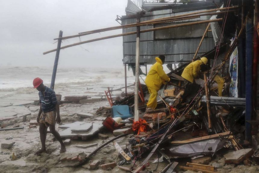 Bangladeshi rescue workers search for survivors after Cyclone Roanu hit Chittagong on May 21, 2016.