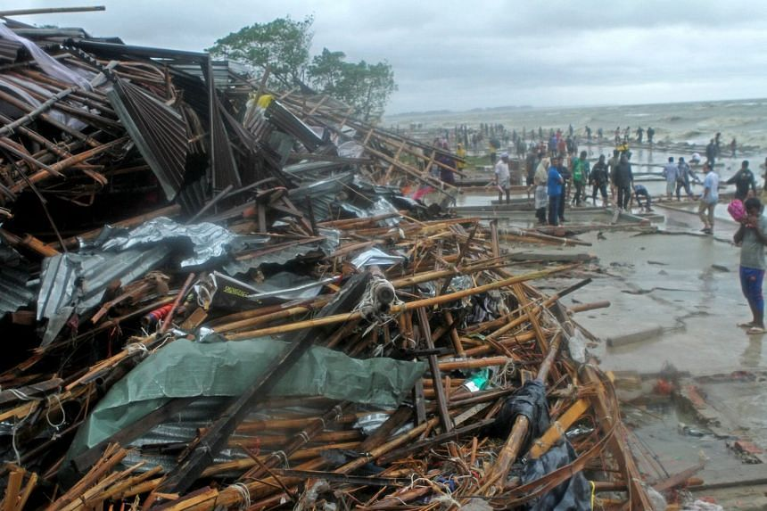 People gather near the debris of the damaged shops following the cyclone Roanu at the Pattenga Sea- Beach in Chittagong, Bangladesh on May 21, 2016.