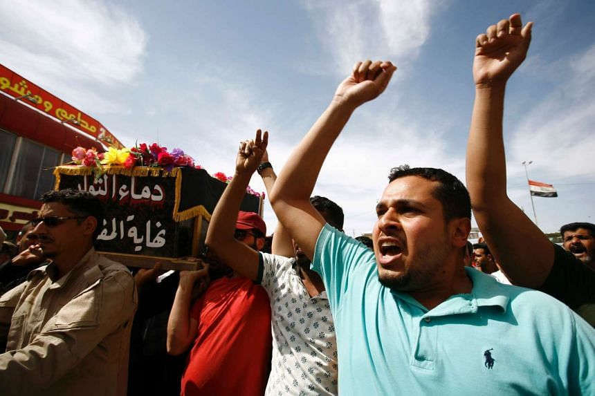 Iraqi men chant slogans as they carry the coffin of an anti-government protester during his funeral in Iraq's holy city of Najaf, on May 21, 2016.