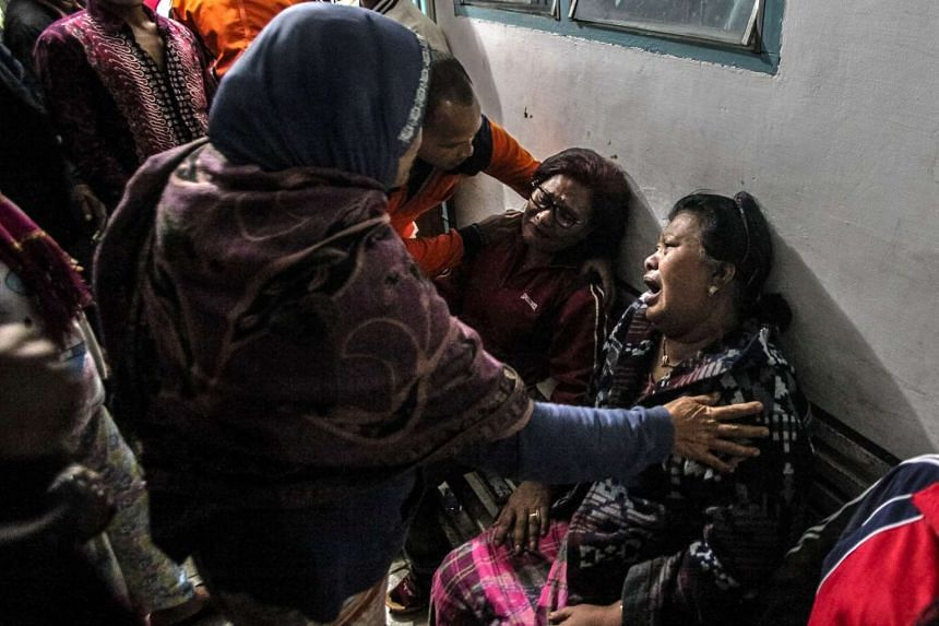 Relatives of the Mount Sinabung eruption victims cry after identifying their relatives, at a hospital in Kabanjahe, Indonesia, on May 21, 2016.