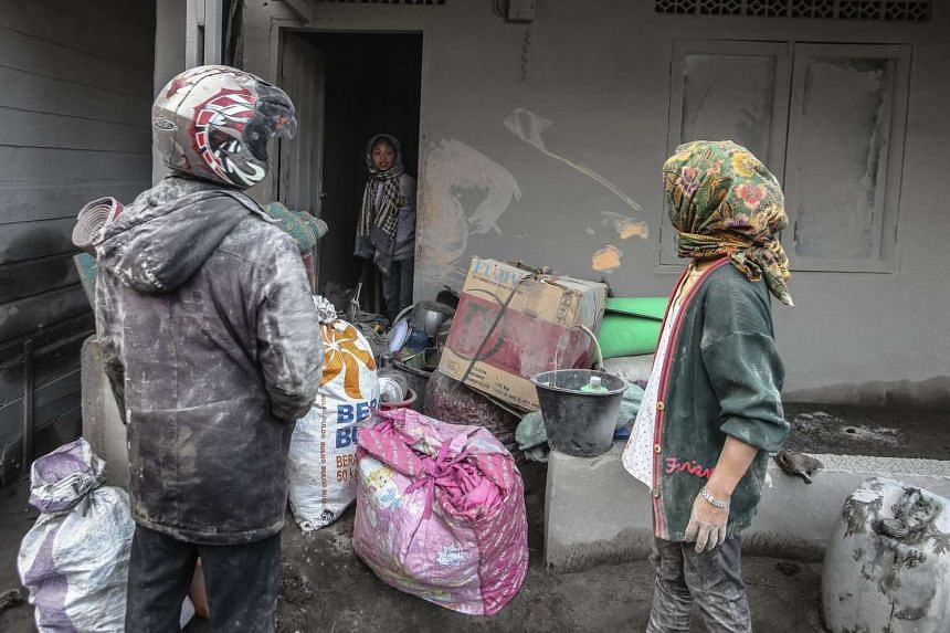 Residents collect their belongings as they evacuate after an eruption of Mount Sinabung volcano in Indonesia, on May 22, 2016.