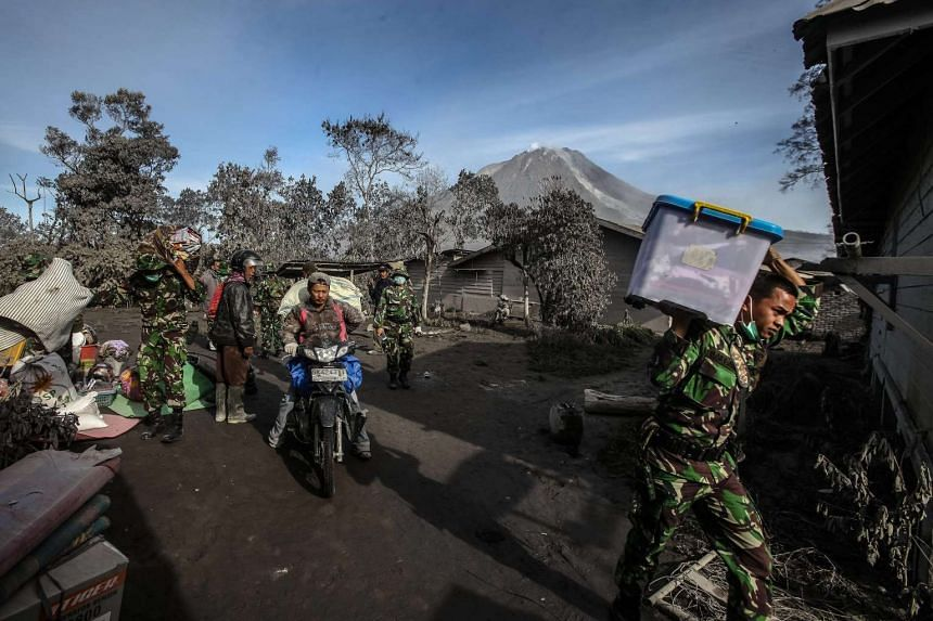Indonesian soldiers carry residents' belongings as they aid in evacuation efforts following an eruption of the Mount Sinabung volcano in Indonesia, on May 22, 2016.