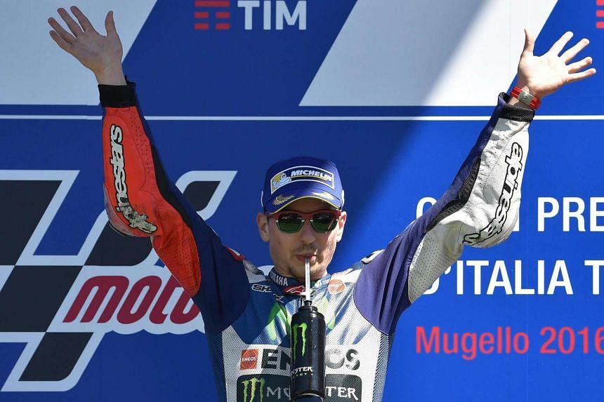 MotoGP rider Jorge Lorenzo celebrates on the podium after winning the Motorcycling Grand Prix of Italy, on May 22, 2016.