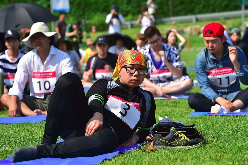 """South Koreans taking part in Seoul's """"space-out"""" competition at a riverside park in Seoul on May 22, 2016."""