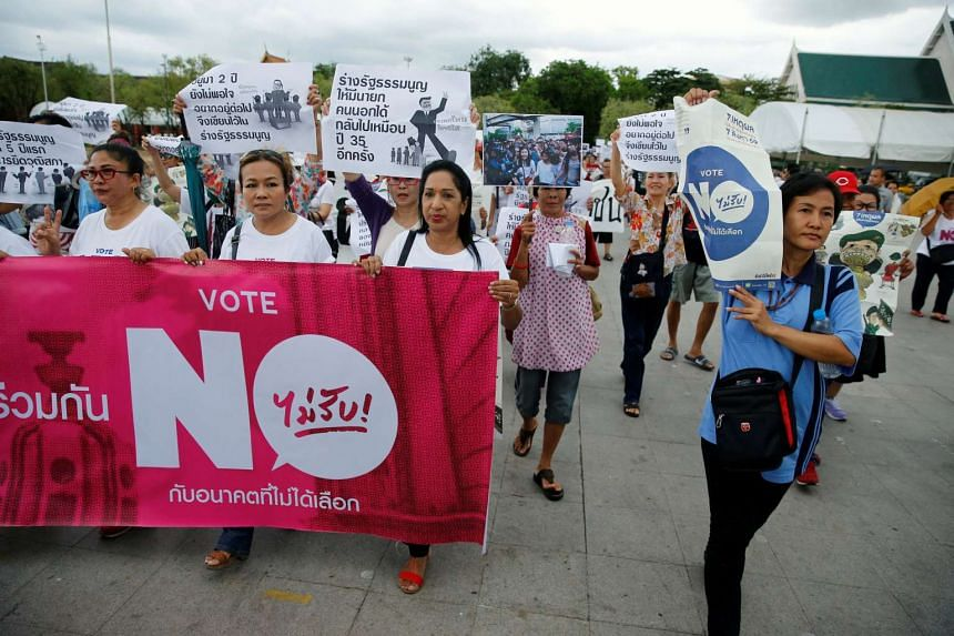 """Anti coup d'etat demonstrators carry a banner promoting to vote """"no"""" at a referendum on a junta-backed draft constitution in Bangkok, on May 22, 2016."""