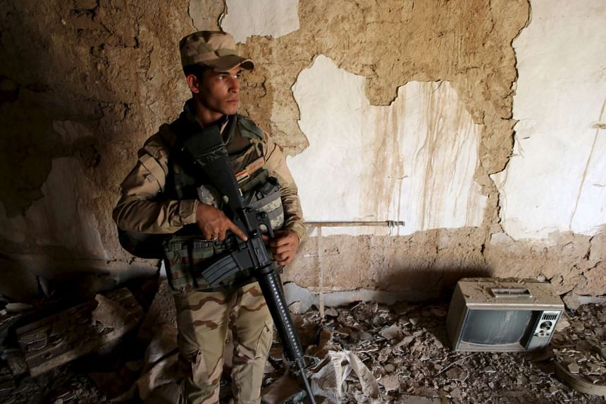 An Iraqi soldier holds his rifle in a building damaged during fight between Iraqi army and Islamic State fighters in a village of Mahana, Iraq, on April 28, 2016.