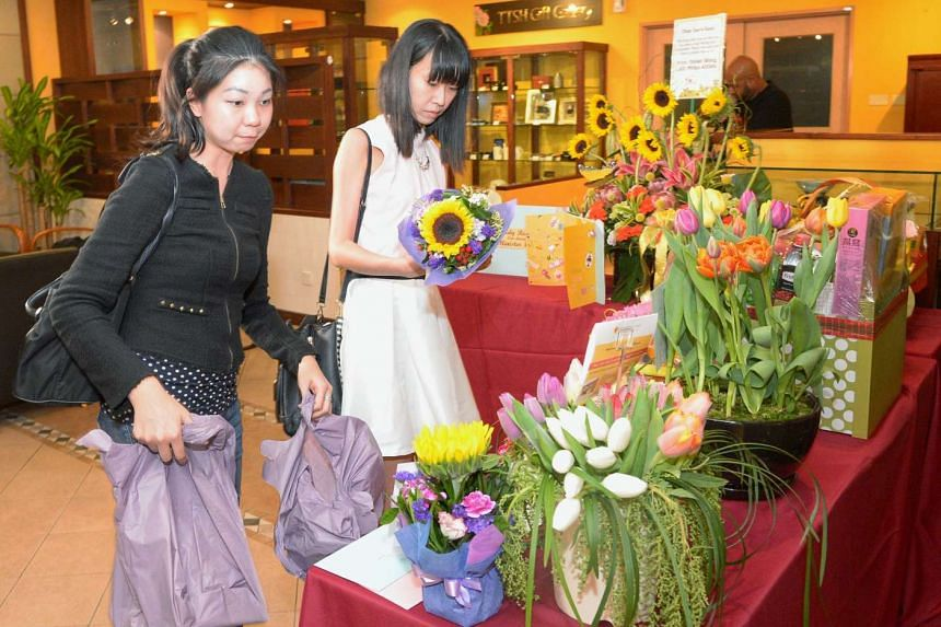 Tampines residents Kathy Goh (left) and Janessa Thng leaving flowers for Finance Minister Heng Swee Keat at Tan Tock Seng Hospital on May 13, 2016.
