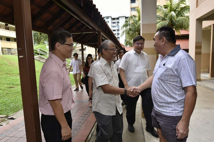 Minister Masagos Zulkifli shaking hands with a Aljunied GRC resident during his visit to Eunos ward.