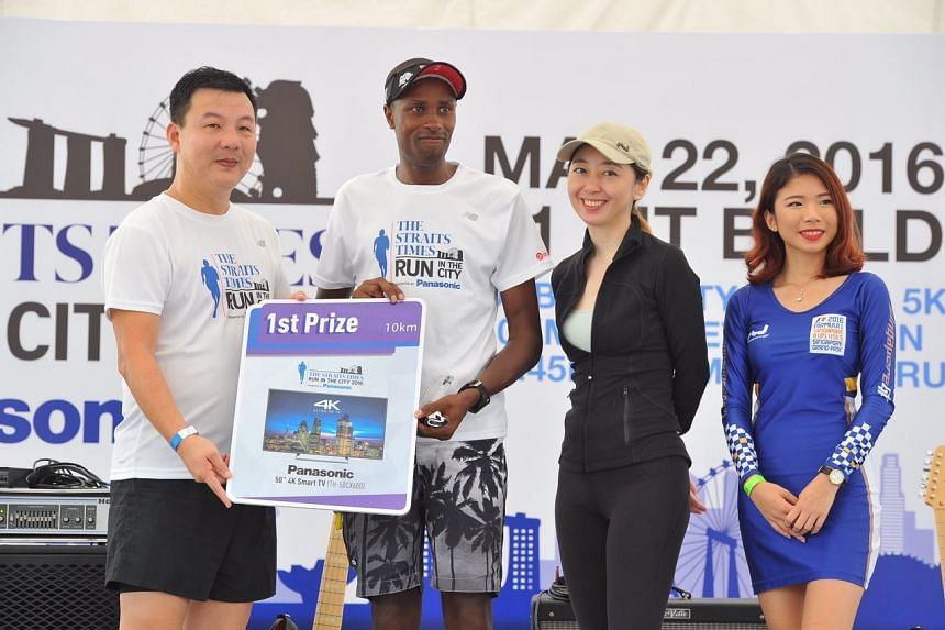 Elija Muturi Karanja (centre) of Kenya accepts the first prize award in The Straits Times Run in the City Men's 10km category.