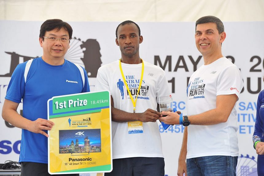Stephen Munhathia Nkubitu (centre) of Kenya accepts the first prize award in The Straits Times Run in the City Men's 18.45km category.