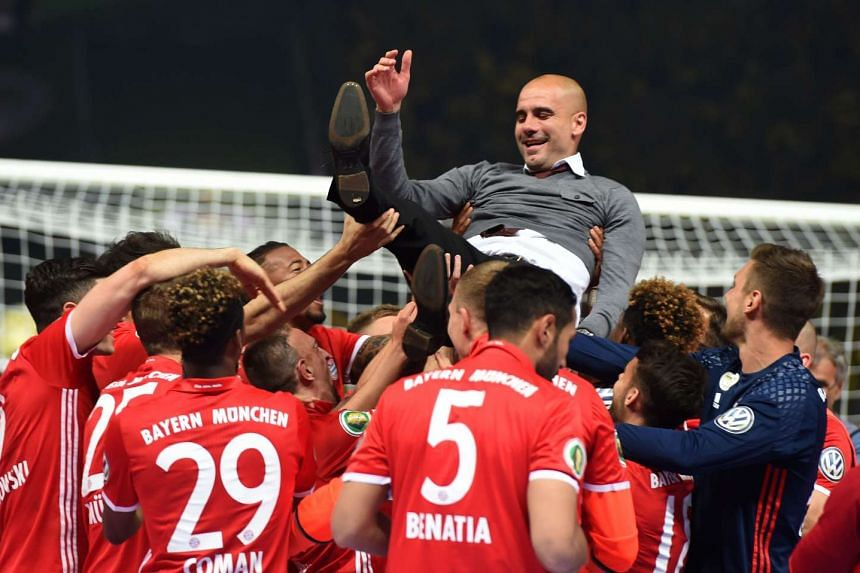 Bayern players throw coach Pep Guardiola in the air after defeating Dortmund.