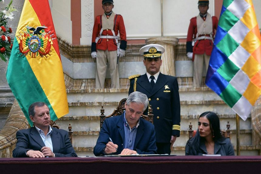 Bolivian Vice President Alvaro Garcia Linera (centre) signing the Law of Gender Identity.